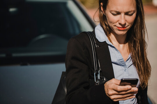 Smiling businesswoman with purse using mobile phone against car on sunny day