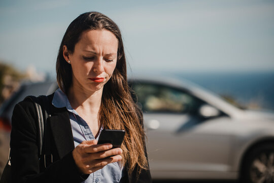 Mid adult businesswoman checking mobile phone on sunny day
