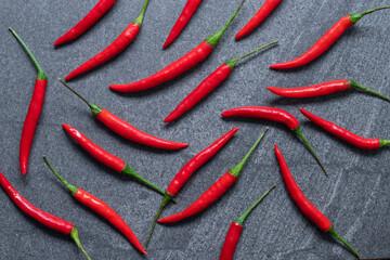 Verschillende verse Red hot chili peper op een donkere zwarte stenen achtergrond, voedselingrediënt concept, bovenaanzicht.