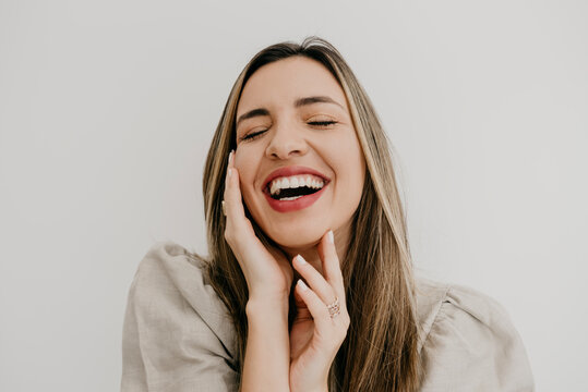 Laughing woman touching cheek with eyes closed against white background