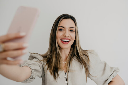 Smiling woman taking selfie through mobile phone against white background