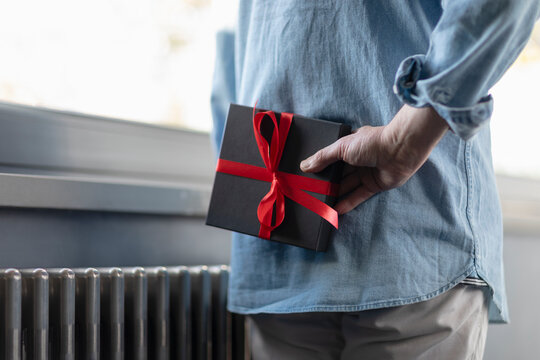 Man holding gift box behind while standing at home