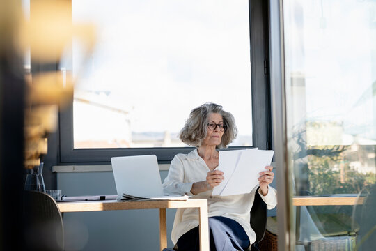 Senior woman checking paper while sitting at home