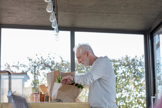 Senior man checking vegetable in bag while standing at home