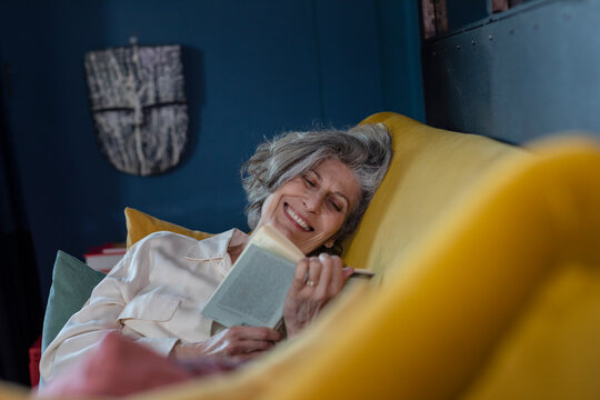 Senior woman smiling while reading book at home