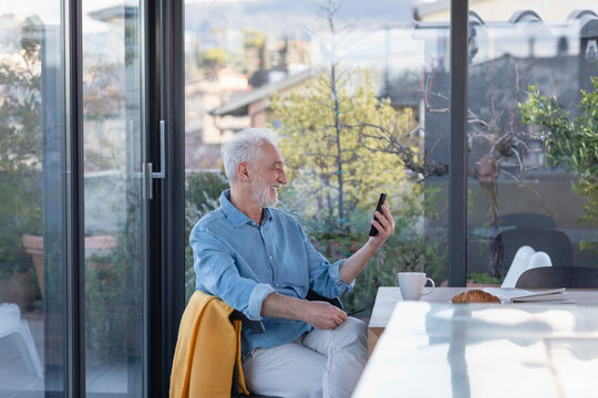 Smiling senior man talking on video call over mobile phone while sitting at home
