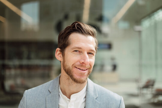 Smiling handsome male professional with brown hair and beard