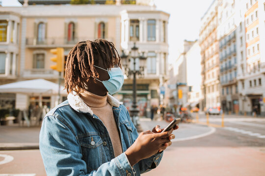 Young man with smart phone standing in city during coronavirus
