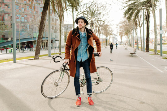 Mid adult man with bicycle standing road in city