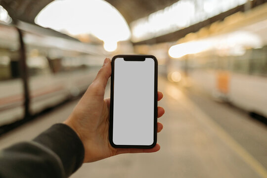 Young man using phone with blank screen at railroad station