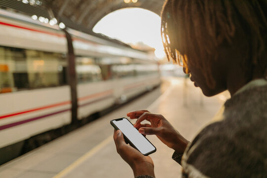Young man using smart phone while waiting at railroad station