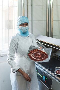 Employee holding package of meat in factory