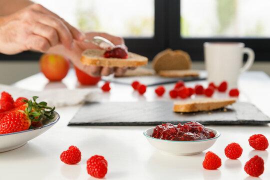 Hands of man preparing breakfast with raspberry jam