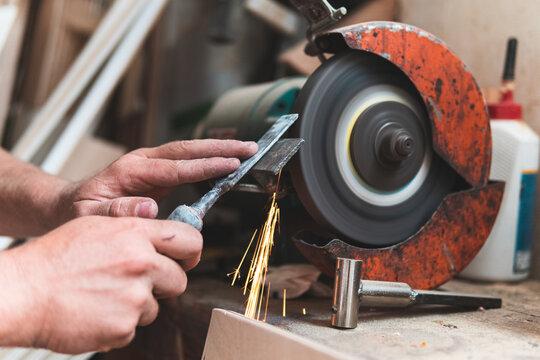 Male carpenter sharpening chisel using grinder in workshop