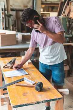 Male carpenter talking on smart phone while working in workshop