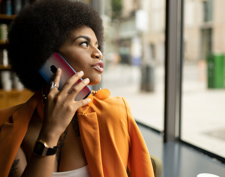 Young woman talking on smart phone in cafe