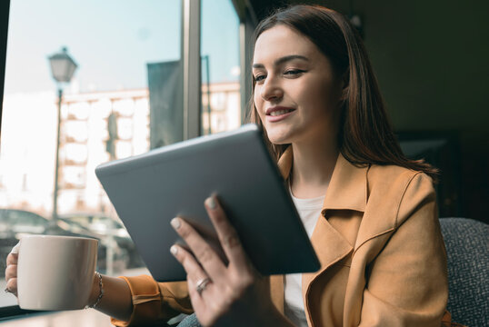 Young woman using digital tablet while sitting at coffee shop