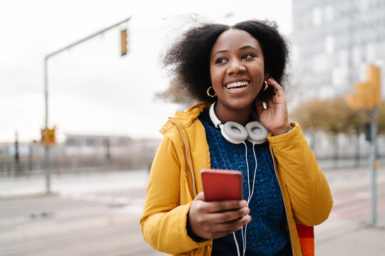 Happy woman looking away with smart phone