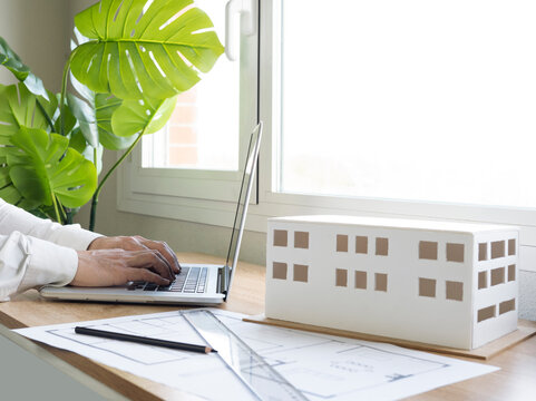 Male design professional working on laptop by architectural model at desk in office