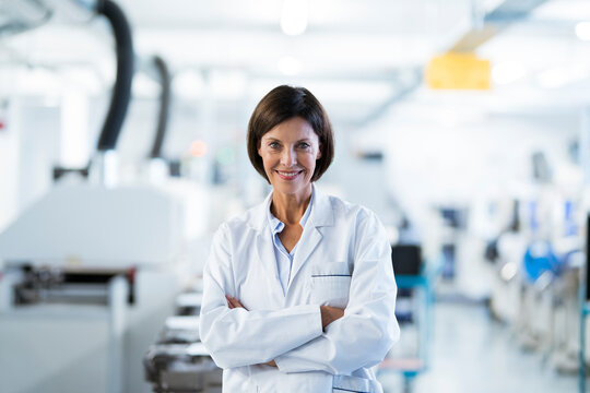 Mature female technician with arms crossed in industry