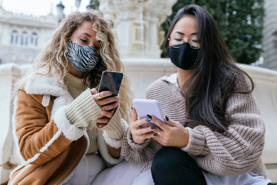 Multi-ethnic women using smart phone wearing protective face mask during pandemic