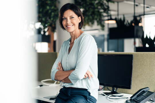 Smiling female entrepreneur with arms crossed against computer in office