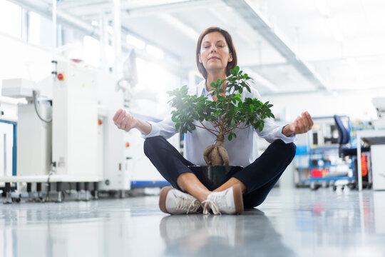 Female entrepreneur meditating while sitting on floor in industry