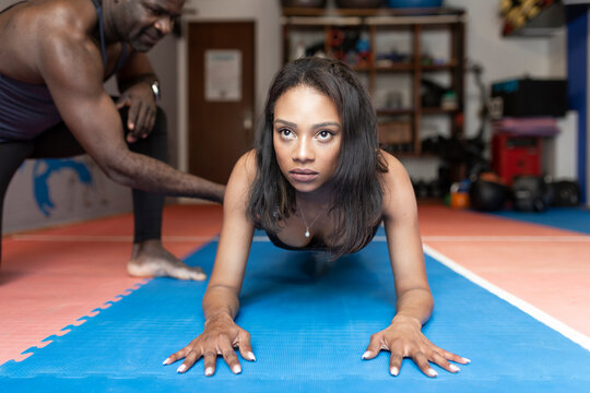 Active woman practicing plank exercise with fitness instructor in gym