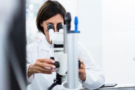 Female scientist using microscope at laboratory