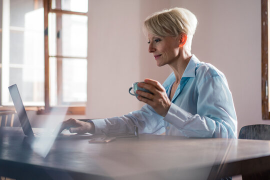 Smiling businesswoman holding coffee cup while working on laptop at desk in home office