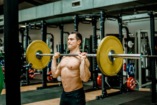 Strong man doing weightlifting exercise at gym