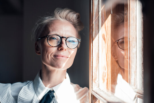 Smiling mature businesswoman looking away while leaning at window in home office