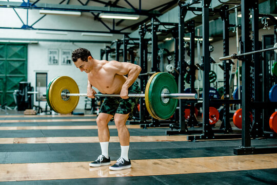 Muscular man lifting weights in health club