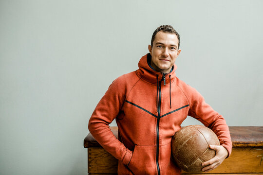 Male athlete with hands in pockets holding medicine ball against wall