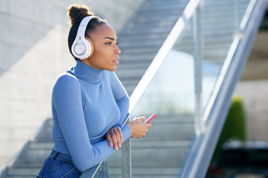 Young woman wearing headphones looking away while standing by railing