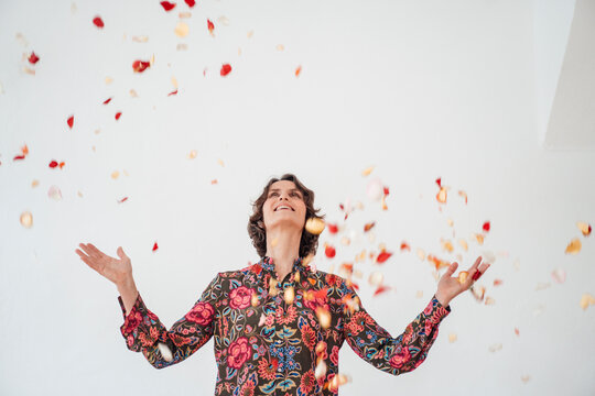 Cheerful woman throwing confetti in front of white wall
