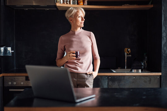 Female entrepreneur with hands in pockets looking away while having coffee in kitchen in home office