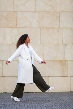 Young woman walking on footpath by wall