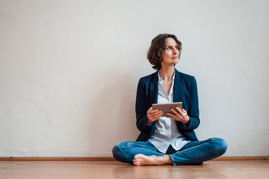 Thoughtful businesswoman with digital tablet sitting on floor in front of white wall