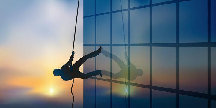 Concept de l'ambition professionnelle avec un homme qui escalade la façade d'un immeuble en grimpant à une corde