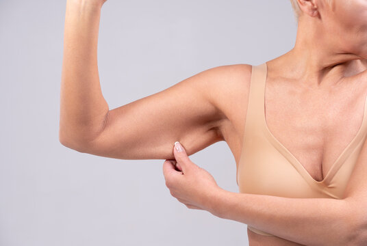 Woman pulling muscle skin while standing against gray background