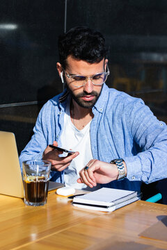 Male entrepreneur with mobile phone checking time while sitting at sidewalk cafe