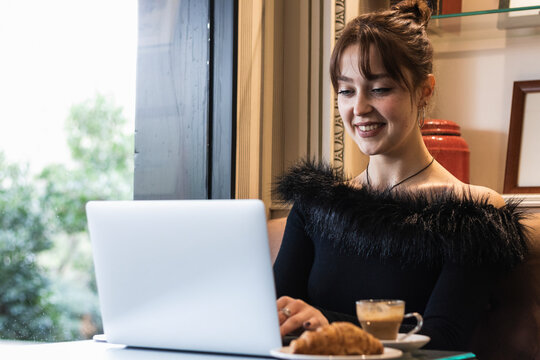Smiling beautiful businesswoman working on laptop while sitting at cafe