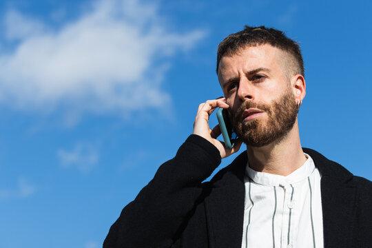 Confused man talking on smart phone against sky