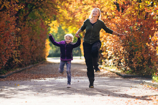 Mother and daughter holding hands and running in park during autumn