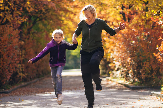 Happy mother and daughter running in park during autumn