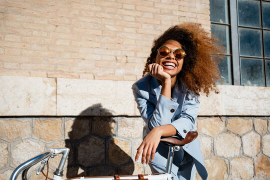 Cheerful young woman in sunglasses leaning on bicycle while standing against building during sunny day