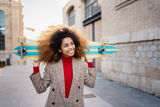 Cheerful woman carrying skateboard on shoulder looking away