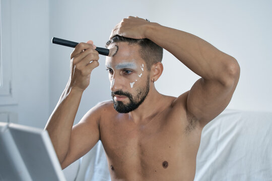 Shirtless man applying face powder with make up brush in front of mirror at home