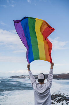 Male tourist holding LGBTQI Flag at El golfo during vacations, Lanzarote, Spain